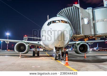 Passenger Airplane At The Telescope Aerobridge At The Airport Night Flight Service