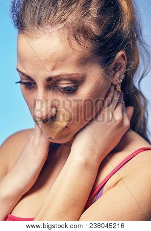 Young woman with his mouth glued with tape. Concept on humiliation and discrimination of women poster