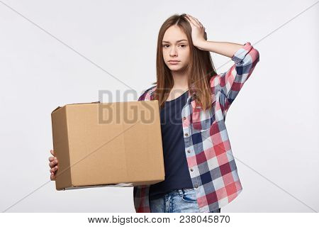 Delivery, relocation and unpacking problems. Discontent young woman holding cardboard box with hand on head poster