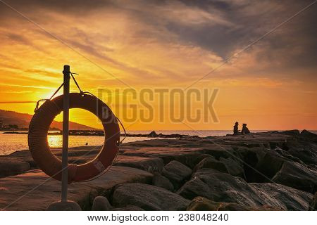 Lovers Meet The Dawn On The Beach. The Sky Is At Dawn. Life Ring For Lovers.