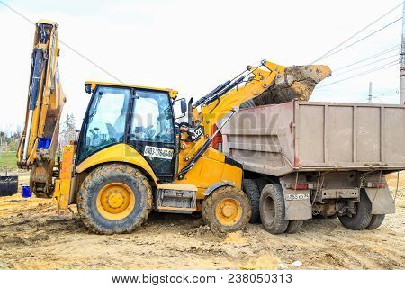 The Tractor Fills Up From A Ladle Sand In The Truck
