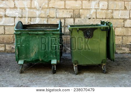 Two Green Trash Dumpsters In Front Of White Brick Wall Front View With Room For Text. Garbage Cans I