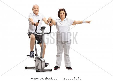 Mature man riding a stationary bike with a mature woman pointing isolated on white background poster