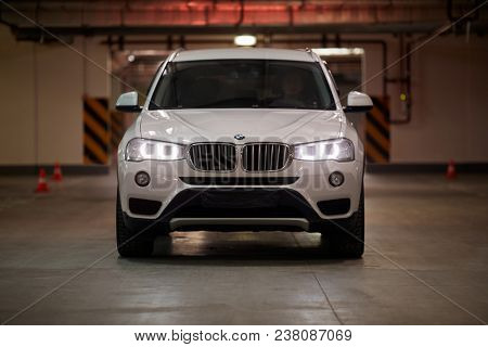 MOSCOW - NOV 17, 2017: White BMW car with man (MR) on driver seat with headlights on at underground parking.
