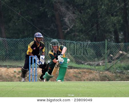 PUCHONG, MALAYSIA - SEPT 24: Guernsey's Tom Kimber bats, watched by Malaysia's Mohd Safiq at the Pepsi ICC World Cricket League Div 6 finals in Kinrara Oval on September 24, 2011 in Puchong, Malaysia.