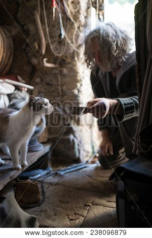 Dark Scene Of Man With Unkempt Long Gray Hair Kneeling On The Floor Feeding Cat From Bowl In Shed.