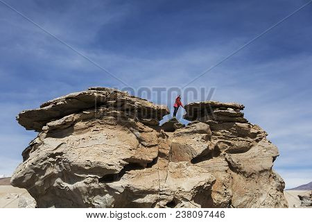 Young Man At Rock Formations Of Dali Desert In Bolivia At Eduardo Avaroa Andean Fauna National Reser