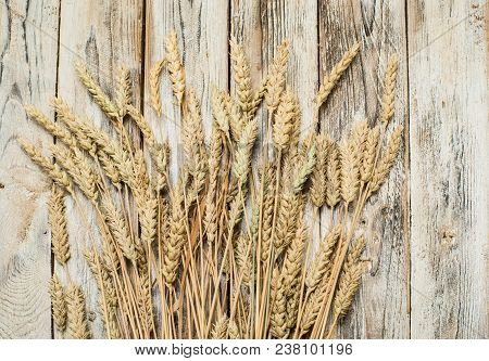 Sheaf Of Wheat Ears On The Wood Background