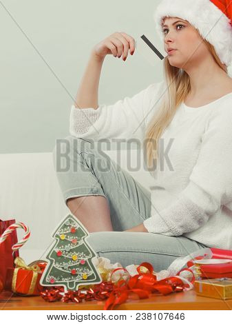 Buying Christmas Gifts Concept. Woman In Santa Hat Holding Credit Card About To Buy Presents.