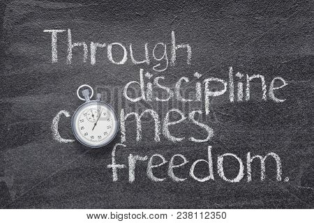 Through Discipline Comes Freedom Quote Handwritten On Chalkboard With Vintage Precise Stopwatch Used