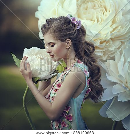 Portrait Of The Beautiful Girl As Thumbelina In A Blue Dress Near The Giant Peony Flowers. Blonde Wi