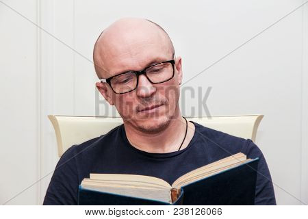 Adult Bald Man In Glasses Reading A Book