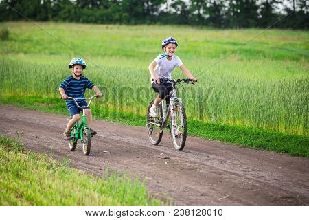 Two Kids Riding On Bikes Together On Rural Road, Outdoors