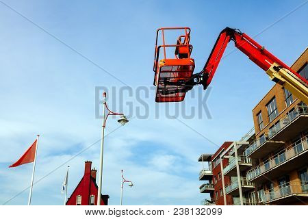 The Used Red Boom Lifts With The Blue Sky Background. Red Lift With A Red House And Red Lights.