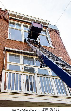 The Used Blue Boom Lifts For Repair And Washing Windows. Lift On The Background Of An Old Brick Hous