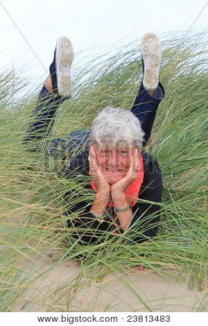 Smiling lady in her seventies laying down outside in the grass.