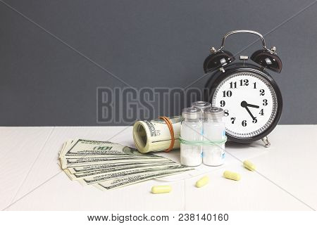 Money Dollar And Drug(pill). Concept Of Medicine.  Alarm Clock For Health. Healthcare Backgound With