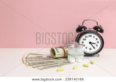 Money And Pills. Concept Of Medicine.  Alarm Clock For Health