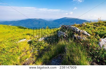 Grassy Meadow With Giant Boulders On The Slope. Mountain Ridge On A Beautiful Sunny Summer Day. Wond