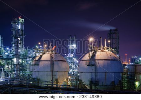 Storage Sphere Tanks In Oil And Gas Refinery Plant With Night, Glitter Lighting Of Petrochemical Pla