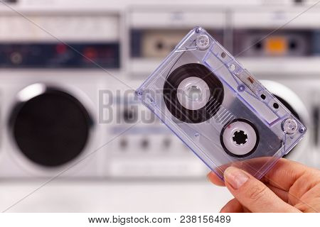 Hand Holding Compact Audio Cassette Tape On Retro Player Background - Shallow Depth