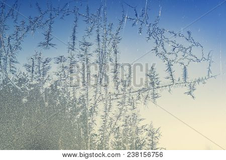 Frost Bites On A Window On A Cold Winter Morning With Blue Color