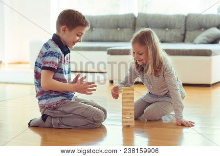 Two Happy Siblings Playing A Game With Wooden Blocks At Home