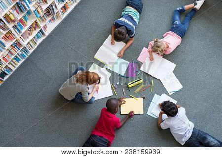 Elementary children lying on the floor and drawing at library. Top view of five multiethnic boys and girls in daycare house drawing on copybook. High angle view of group of kids with colorful pencils.