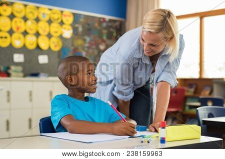 Teacher helping young african boy with homework. Happy teacher helping her student at elementary school. Portrait of woman teaching to schoolchild in classroom.