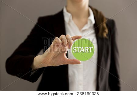 Young Businesswoman Holding Virtual Button Start. New Start, Beginning, Business Concept