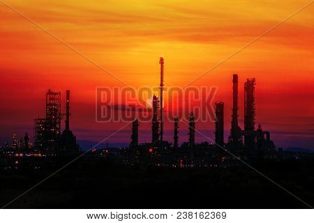 Silhouette Of Oil Refinery At Twilight Background.