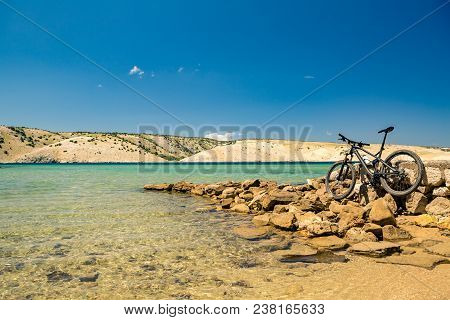 Mountain Bike Over Sea, Mountains And Blue Sky On A Rocky Beach, Summer Day Landscape. Idea For Vaca