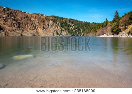 French Landscape - Vosges. The Small Lake Lac Blanc In The Vosges With Rocky Shore In The Background