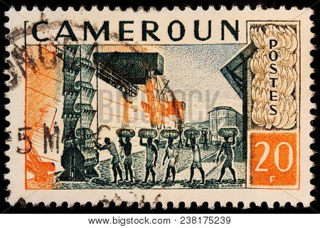 Luga, Russia - October 7, 2017: A Stamp Printed By Cameroon Shows Loading Of The Vessel Carrying Cam
