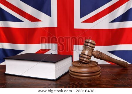 Still life photo of a gavel, block and law book on a judges bench with the United Kingdom union jack flag behind.