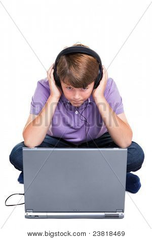 Photo of an 11 year old school boy wearing headphones sitting with a laptop computer, isolated on a white background.