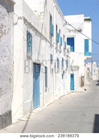 Deserted Street Of Mahdia With Blue Doors And Lattices On The Windows. Tunisia