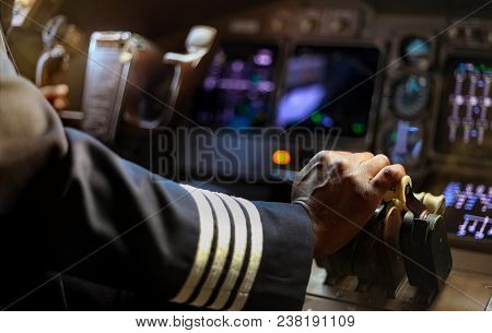 Cropped Hands Of African Pilot Flying A Commercial Airplane, Cockpit View Close Up Of Hands