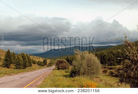 Road In Forest. Wide Steppe With Yellow Grass Under A Blue Sky With White Clouds Sayan Mountains Sib
