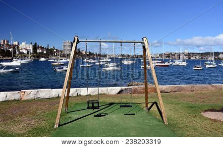 Balgowlah, Australia - Feb 4, 2018. Empty Swings On Chains For Two In A Playground At Fourty Baskets