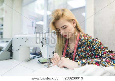 Beautiful Girl Works On A Sewing Machine. Seamstress Creates Wear On The Sewing Machine. Focus On Th