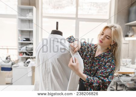 Young Female Dressmaker Works Inserts Needles Into The Clothes That Are On The Mannequin. Fashion De