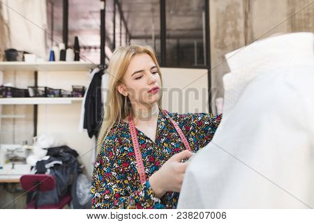 Portrait Of Young Designer Shane And Work In Her Own Fashion Studio. The Cute Girl Is Standing By Th