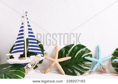 Summer, Vacation Concept. Decorative  Wooden Toy Boat, Sea Star And Tropical Plant Leaves  On White