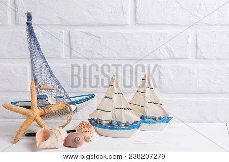 Coastal Living  Decorations.  Decorative Boats, Shells And Sea Stars  Near By White Brick Wall. Sele