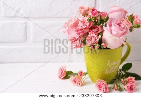 Pink Roses Flowers In Green Cup Against  White Brick Wall. Floral Still Life.  Selective Focus. Plac