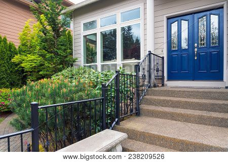 House With Blue Double Doors Concrete Steps Entry By Landscaped Front Yard Garden