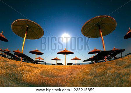 Summer landscape of beach resort with sand and straw umbrellas under sun light