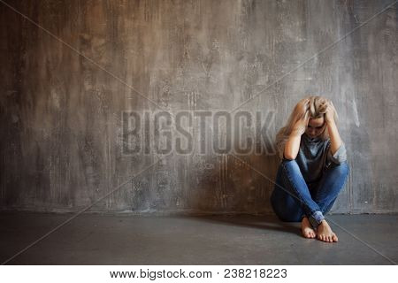 Depressing Girl. Sits On The Floor. Depression And Chronic Fatigue. Young Beautiful Blonde In A Gray