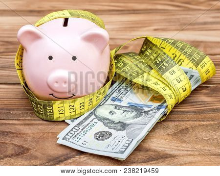 Piggy Bank With Measuring Tape And Money On Wooden Background.